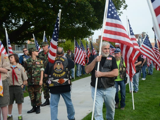Flag bearers flow into place during the 9/11 memorial on Monday night at McCamly Park.