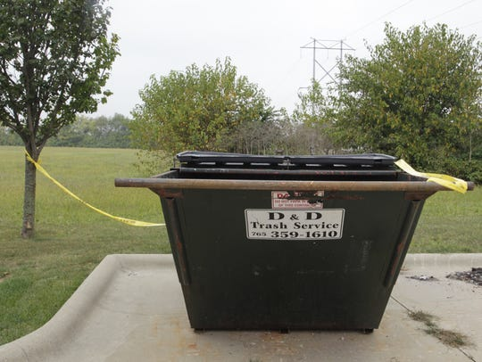 Police tape surrounds a dumpster Monday, Sept. 18,