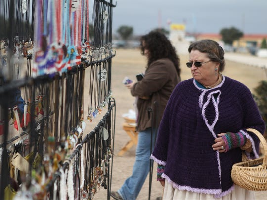 Re-enactor Patricia Hopkins browses through rows of necklaces as she shops around one of the many tents on the parade ground at the annual Christmas at Old Fort Concho.