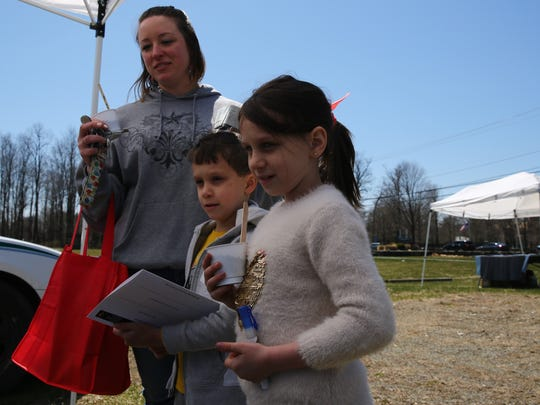 Hyde Park resident Ashley Hajosch stops by a booth with her stepchildren, Xander, 6, and Chloe Bradford, 8. The kids planted seeds in Styrofoam cups filled with dirt.