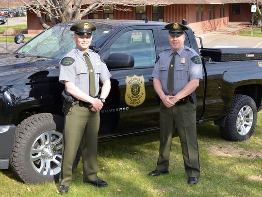 Michigan Conservation Officers Kyle McQueer, left, and David Miller stand near McQueer's patrol truck at the Michigan Department of Natural Resources' Customer Service Center in Marquette. The two officers rescued a Baraga County woman May 3 from a 70-foot cliff above the Lake Superior shoreline near L'Anse.