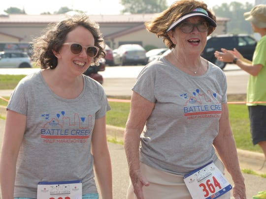 Grace Shevick (right), 71, walks across the finish line with her friend, Renee Walters, at the Battle Creek Half Marathon on Saturday, June 30, 2018.