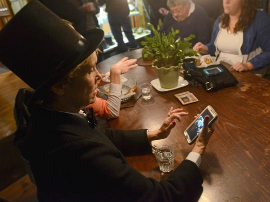 Alice Rieves, of Kimball Township, dresses up for the Groundhog Day festivities and browses photos of Punxsutawney Phil on her phone Monday at the Exquisite Corpse coffee house.