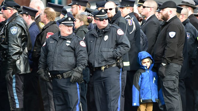 A child with with police officers during a funeral for slain Trooper Landon Weaver is held in Altoona  Thursday, January 5, 2017. Trooper Weaver was killed by a gunman while responding to a call for a domestic dispute.