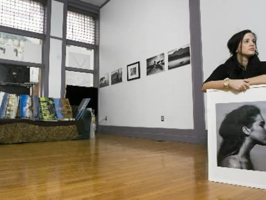 Elena Jasic with one of her photographs, while another exhibit is in the process of coming down at the Jane Plus Neal Images LLC gallery at 9 W. Philadelphia Street in York. The exhibit 'Grades of Vanity' opened Feb 4.