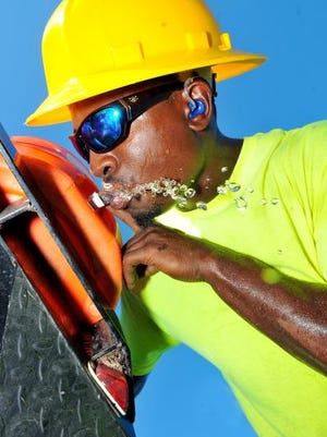 Demetrius World of Rockledge who works for Green Leaf Landscaping and Irrigation tries to stay hydrated as his crew trims tree along Ridgewood Ave in Cape Canaveral Tuesday afternoon in the  unusually hot weather for November .