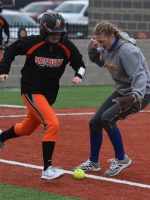 Mountain Home first baseman Grace Gilbert (right) lets Hope Lange's bunt attempt go foul during the Lady Bombers' 8-0 loss to the Batesville Lady Pioneers on Tuesday night at McClain Park.