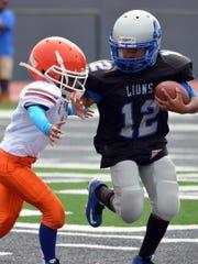 Julian Nichols of the Canton Lions junior freshman team runs with the ball.