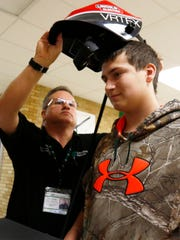 Tony Schmidt, director of education at Schuette Metals, sets up sophomore Allen Schidell for a virtual welding competition at D.C. Everest Senior High School in Weston on Feb. 3, 2017.