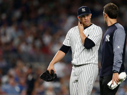 New York Yankees pitcher Luis Cessa, left, walks off the field with a trainer after an injury during the fifth inning of a baseball game against the New York Mets, Monday, Aug. 14, 2017, at Yankee Stadium in New York. (AP Photo/Rich Schultz)