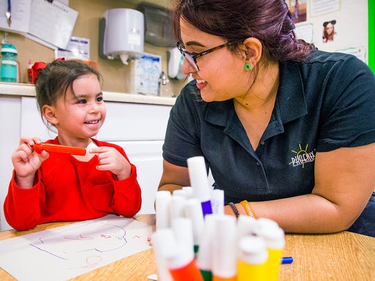 Assistant teacher Teresa Neri works with 4-year-old Amina Valdez during a pre-kindergarten class at Phoenix Day on Dec. 1, 2017.