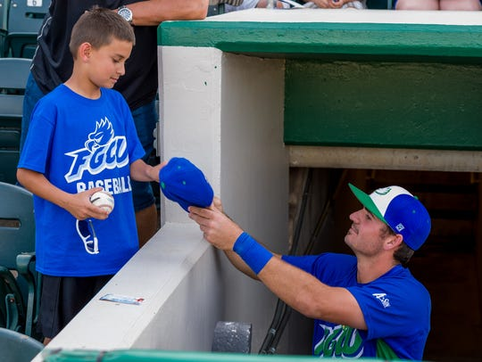 Jake Noll signs an autograph during FGCU's game against