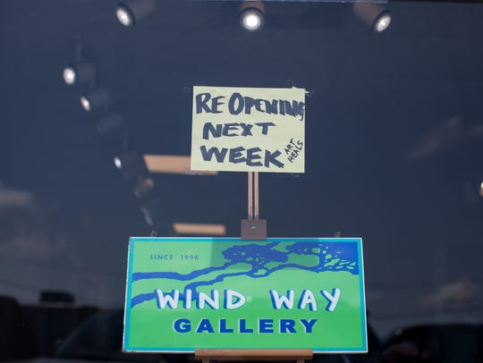 "A sign in the window at Wind Way Gallery reads ""ReOpen"