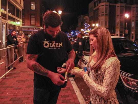 """Door man Mike Dillon places a wristband on a patron's arm during The Queen's """"Drake Night"""" last month. Identification is now checked by security on the sidewalk instead of inside the theater."""