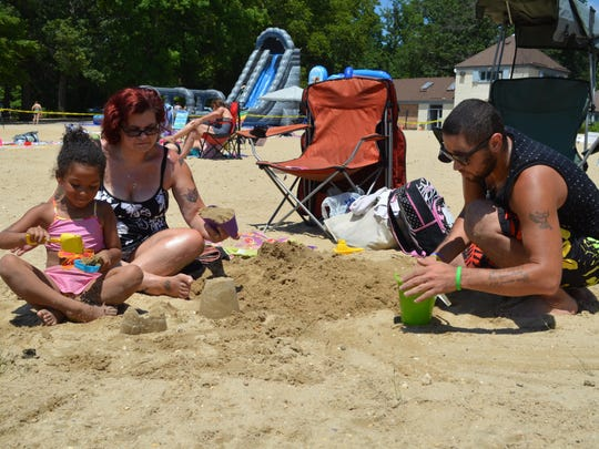 Asia Berrios, 6, Carmelo Shaud and Henry Shaud, all of Elmer build sandcastles at the Parvin State Park beach.