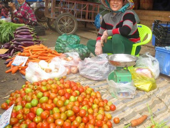 Produce vendors at the outdoor market in Sa Dec, Vietnam.