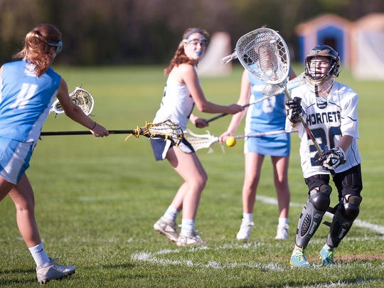 Essex goalie Madi Larson, right, makes a save against South Burlington's Caroline Desautels during Tuesday's high school girls lacrosse game in Essex.
