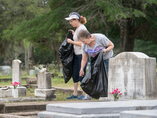 Volunteers Sally Simpler, left, and Janet Dorrell pick up debris Thursday, June 1, 2017, during the cleanup effort in memory of longtime Milton Historic Cemetery manger Bill Bledsoe at the cemetery.