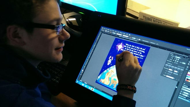CovCath senior Luke Rolfsen draws on a Wacom Cintiq digital drawing tablet's screen as he designs the school Christmas card sent out to more than 2,000 homes and businesses.