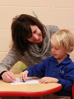 Teacher Dawn Shelton helps Will Cooper color trees and a snowman in her 2-year-old class at Jackson Christian School.