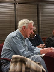 County commissioner Jimmy Arnold reads a proposed referendum at a meeting Tuesday between members of the School Board and the Madison County Commission.