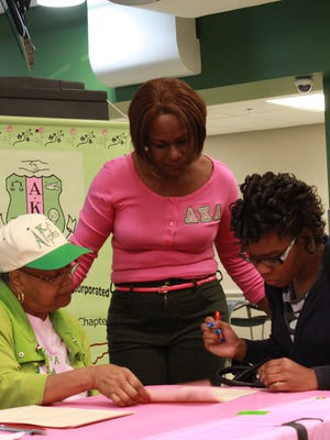 Mary Platt and Patricia Beasley help Shainia Perry register to vote Tuesday at Jackson State Community College.