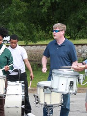Past and present members of Jackson Central-Merry High School's marching band practice at the school Thursday.