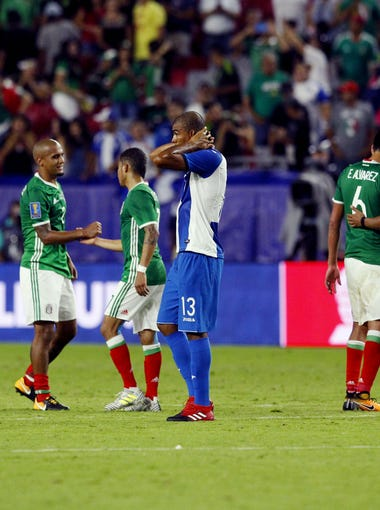 Honduras' Sergio Peña (13) puts his hands on his head while Mexico players celebrate the win after the CONCACAF Gold Cup quarterfinal soccer match in Glendale, Thursday July 20, 2017.