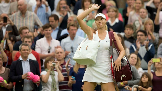 Maria Sharapova waves to the crowd after her match against Alison Riske on Day 6 of the 2014 Wimbledon Championships at the All England Lawn and Tennis Club.