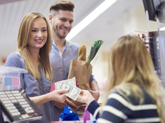 young woman giving cash to cashier in grocery store