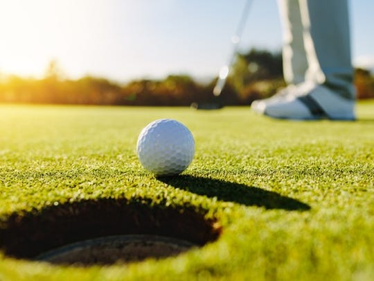 Close-up of a golf ball rolling towards the hole and the shoes of the putter in the background