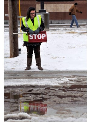 Kayley Lowe, an instructional aide and crossing guard at Bowie Elementary School, measures the depth of the slushy ice melt flowing down Jeannette Street Wednesday. Fortunately for Lowe, no students came by to cross the street as most had already been picked up by parents earlier in the day or when school was let out early at 2:30 p.m. due to Wednesday's ice storm.