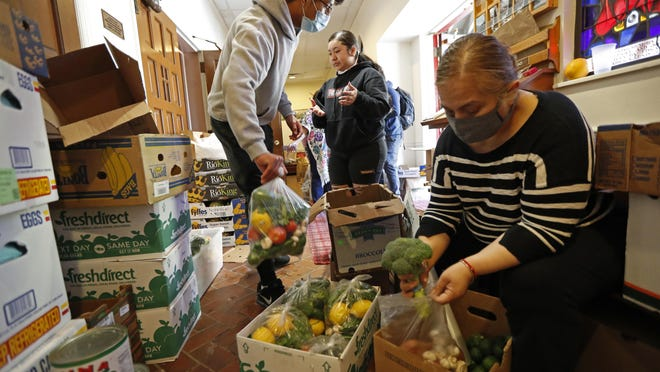Laura Porras, right, prepares bags of fresh vegetables as Justin Ruiz, 17, left, and Porras's neice Ana Karen Porras, 14, help in the vestibule at Lutheran Church of the Good Shepherd in the Bay Ridge neighborhood of Brooklyn May 12 in New York. The effort, which started two months ago, is coordinated by the Brooklyn Immigrants Community Support mutual aid group who saw a need for emergency food aid for undocumented immigrants, who couldn't apply for or receive government assistance in the wake of shutdowns caused by concerns over the spread of the new coronvirus.