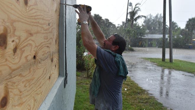 """Randy Schifano, a plumber by trade and resident of the Pearly Sands apartments along Hernando Street on South Hutchinson Island, helps prepare the apartment building on Friday, Sept. 8, in Fort Pierce for the arrival of Hurricane Irma. """"I'm used to them, I've been here since 2003, so I went through the four (hurricanes) back then, sometimes we just chip in and help out,"""""""