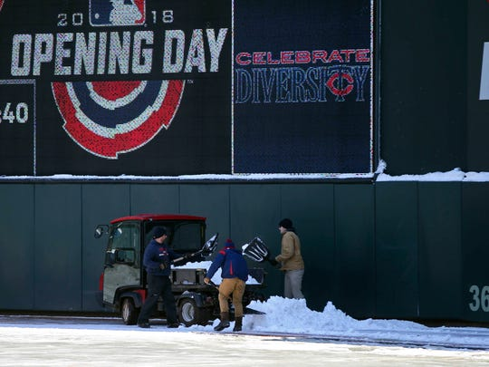 Grounds crew workers remove remaining snow in right field at Target Field in Minneapolis on Wednesday.