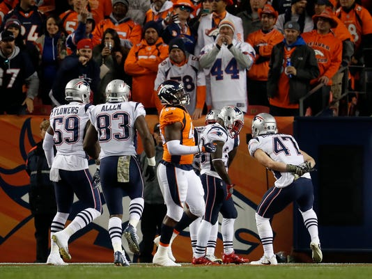 New England Patriots running back Dion Lewis, center, celebrates his kick-off return for a touchdown against the Denver Broncos with teammate tight end Jacob Hollister (47) during the first half of an NFL football game, Sunday, Nov. 12, 2017, in Denver. (AP Photo/David Zalubowski)