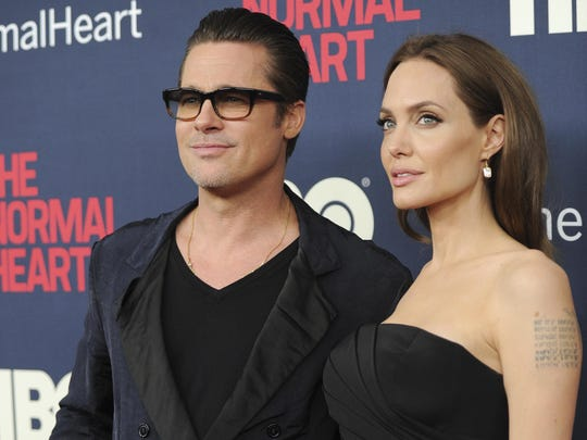 """In this May 12, 2014 file photo, Brad Pitt and Angelina Jolie attend the premiere of HBO Films' """"The Normal Heart"""" at the Ziegfeld Theatre in New York. Jolie and Pitt are officially single, though more work is left before the terms of their divorce are final."""