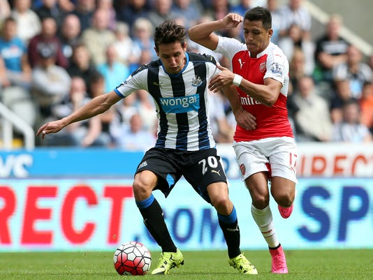 Newcastle United's Florian Thauvin, left, vies for the ball with Arsenal's Alexis Sanchez, right, during their English Premier League soccer match between Newcastle United and Arsenal at St James' Park, Newcastle, England, Saturday, Aug. 29, 2015. (AP Photo/Scott Heppell)