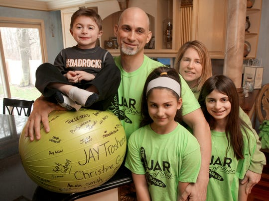 Jamesy Raffone, 6, is shown sitting on a signed exercise ball with his parents, Jim and Karen, and sisters Julia (left), 10, and Mariana, 12, in their Manalapan home. Jamesy has a rare, terminal form of muscular dystrophy called Duchenne.