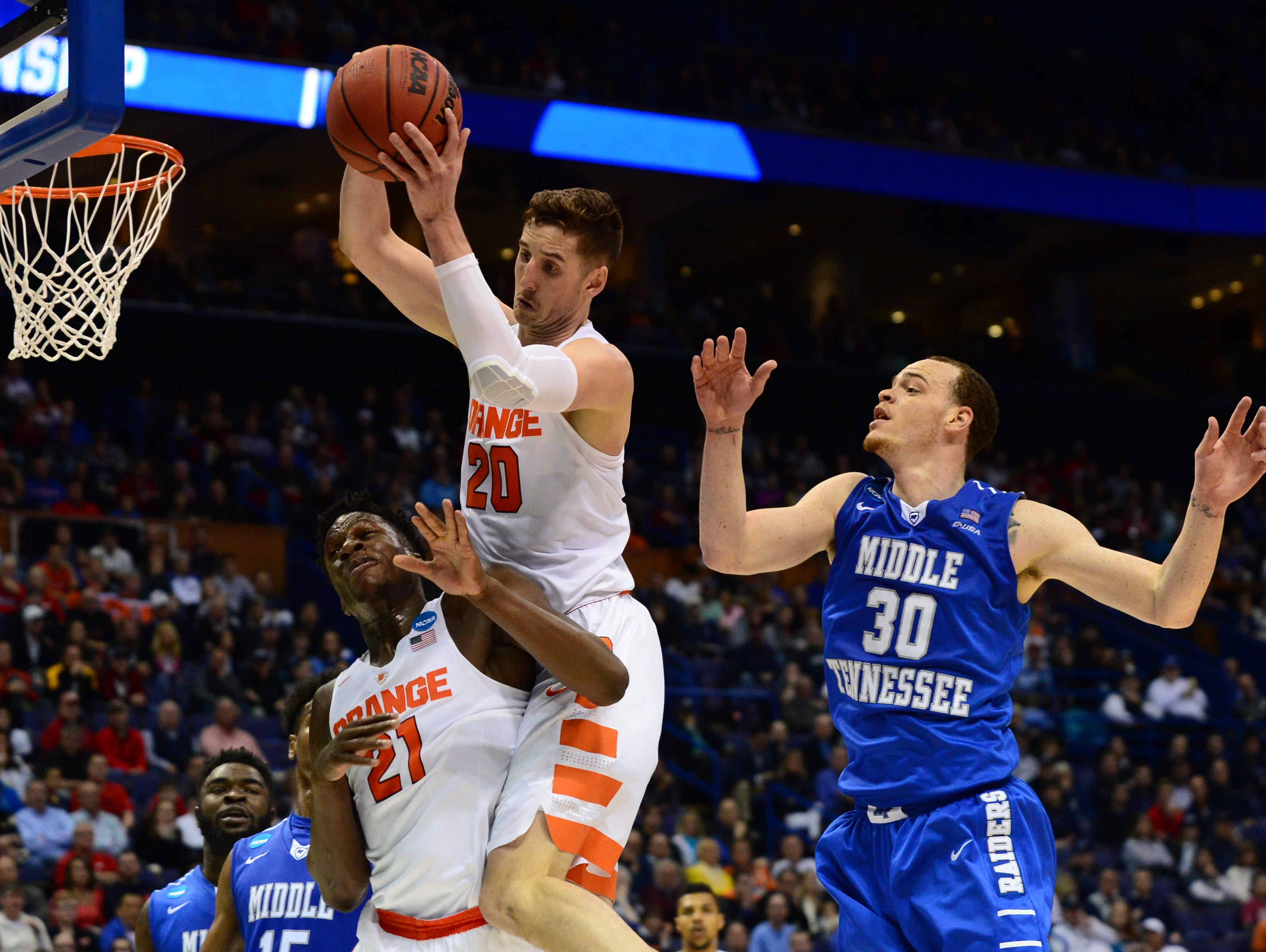 Syracuse's Tyler Lydon, center, an Elizaville native, falls on forward Tyler Roberson as Middle Tennessee's Reggie Upshaw looks on at Scottrade Center in St. Louis, Missouri Sunday.