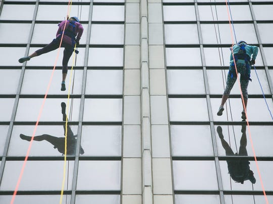 Melissa Renzi (left) and Lynette Mullnack rappel down 17 stories at the TD Bank building in downtown Wilmington to raise money and awareness for Special Olympics Delaware.