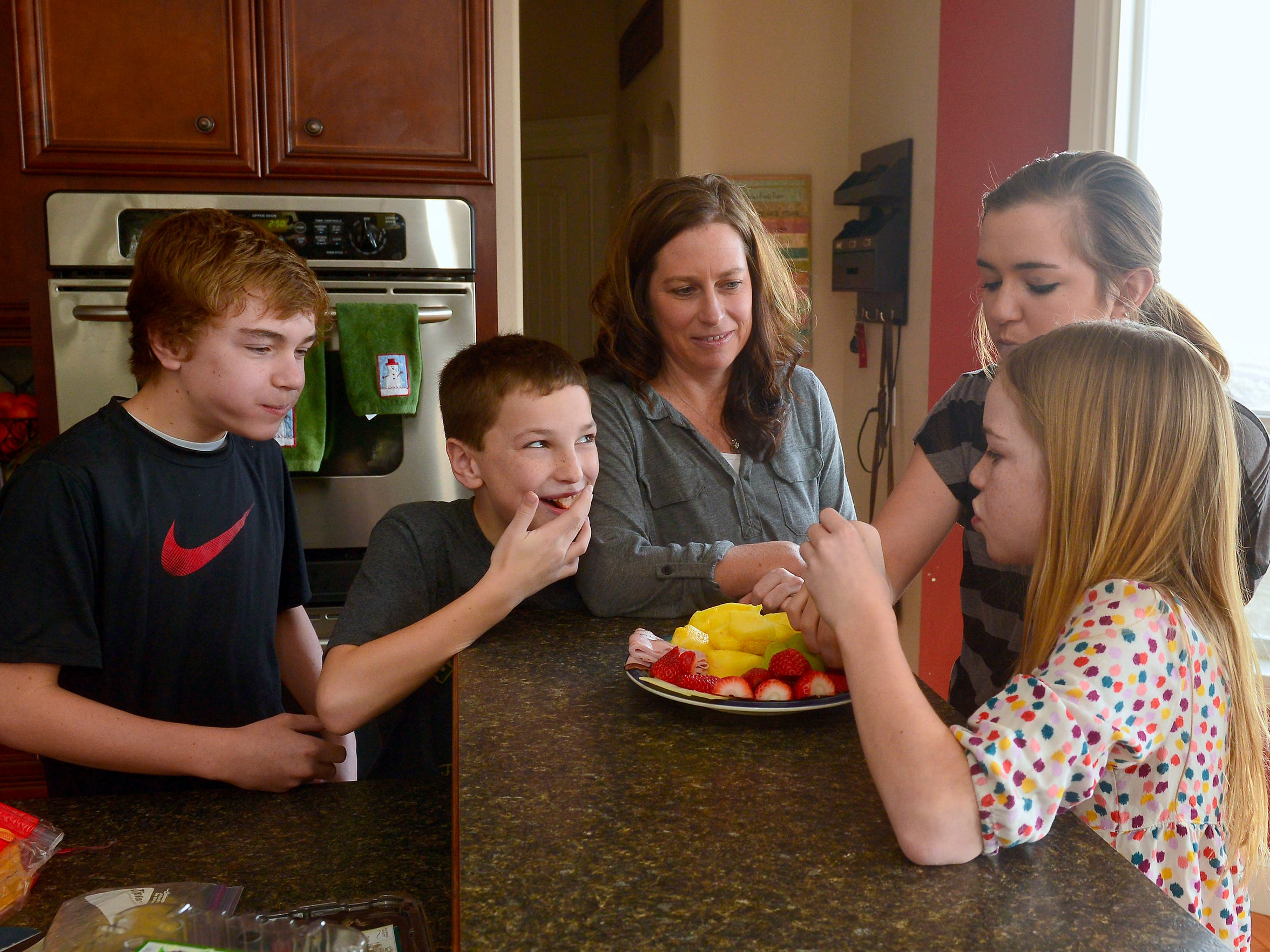Kelli Gardner eats a snack with her children.