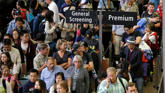 Travelers stand in long security lines at Seattle-Tacoma International Airport on Aug. 15, 2015.