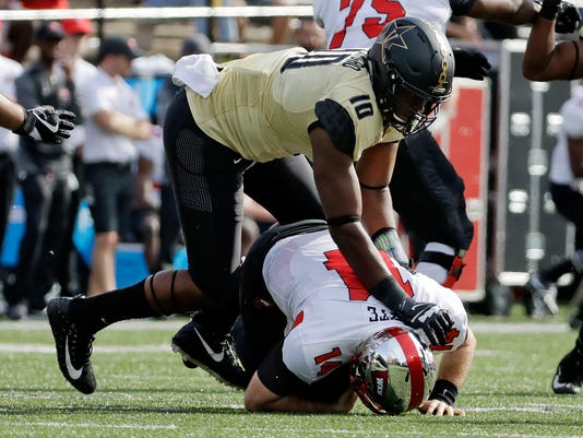 Western Kentucky quarterback Mike White (14) is sacked by Vanderbilt defensive lineman Dayo Odeyingbo (10) for a 7-yard loss in the second half of an NCAA college football game Saturday, Nov. 4, 2017, in Nashville, Tenn. Vanderbilt won 31-17. (AP Photo/Mark Humphrey)