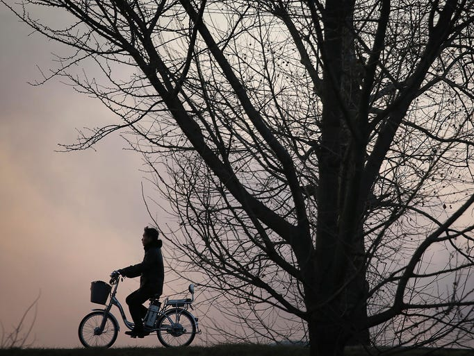 A man rides his electric bicycle along the Taedong