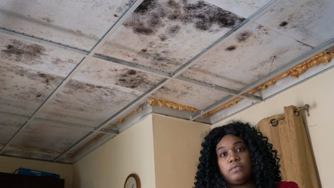 Shanica James in her apartment at Olympic Gardens in Brick. The apartment has pervasive mold on the ceiling.