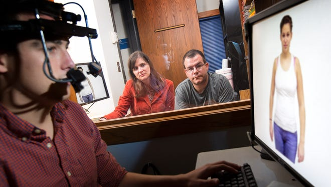 Sarah Gervais, assistant professor of psychology and women's studies at the University of Nebraska in Lincoln, and Mike Dodd, associate professor of psychology, watch as graduate student Gerald McDonnell demonstrates the eye-track hardware and software used for the eye-tracking research.