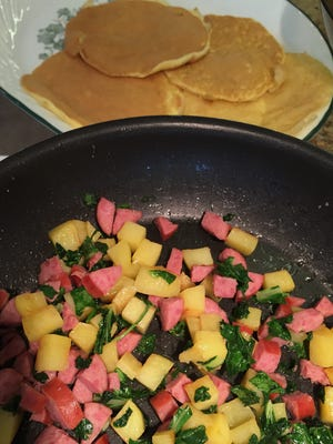 A saute of potatoes, sausage and spinach forms part of the filling of German Breakfast Burritos, along with egg patties, which look a bit like pancakes.