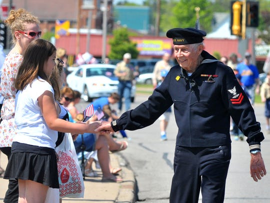 A parade spectator shakes the hand of a retired war