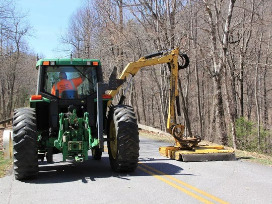 Blue Ridge Parkway staff are using a boom ax tractor